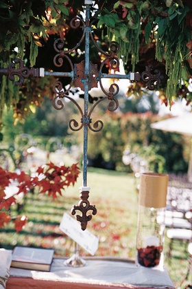 Wrought iron cross hanging from outdoor ceremony structure
