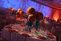 Wedding reception table with three centerpieces of colorful flowers
