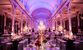 Vibiana wedding reception room shot with chandeliers in gold frames, mirror tables, purple lighting