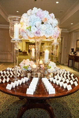 large pastel floral centerpiece with candles at escort card table