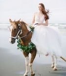 bride rode a horse with a green wreath garland around its neck on the beach in her wedding gown