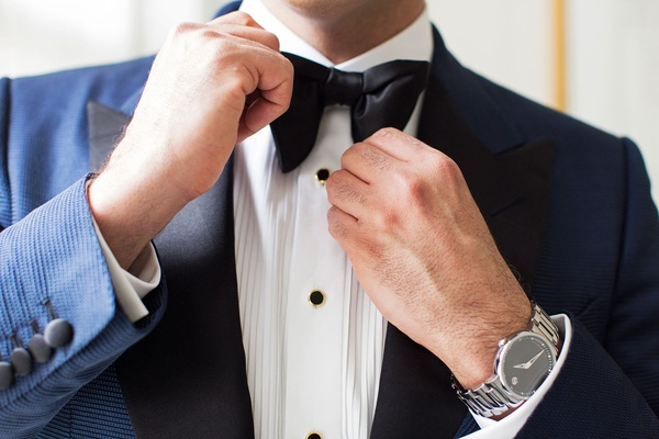 Groom with navy suit white shirt black buttons black bow tie movado watch