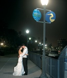 Bride and groom embrace at the marina at night.