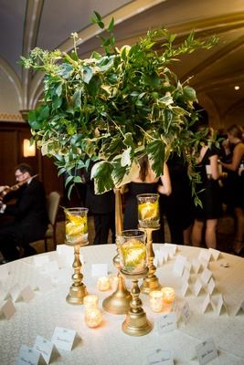 greenery arrangement with ivy, gold candle holders with ferns, escort card table