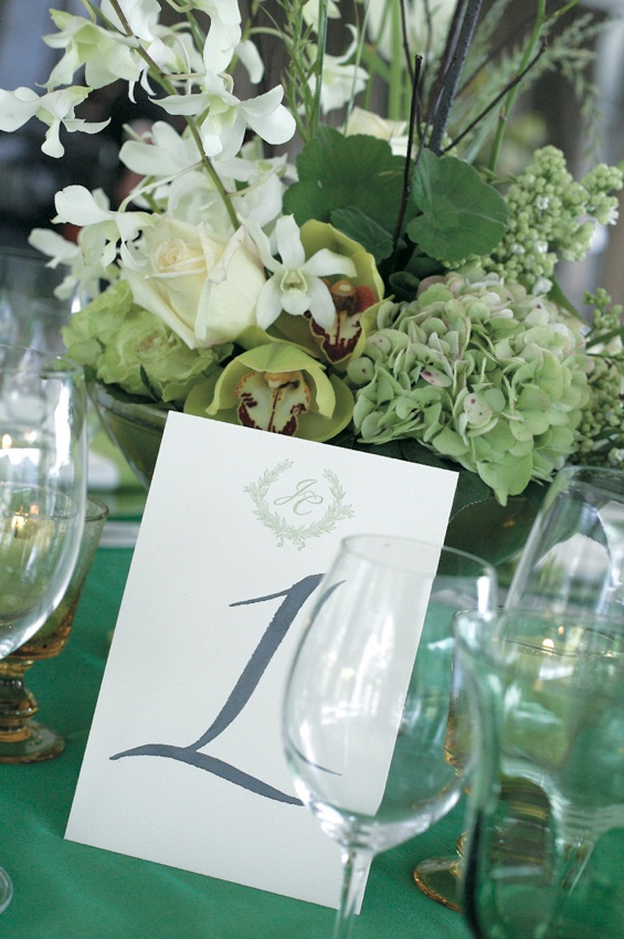 Wedding reception table with hand drawn number and bouquet of green and white flowers