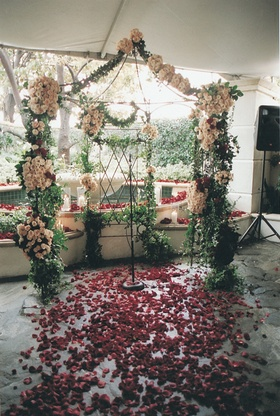 garlands of white flowers and red rose petals decorate ceremony