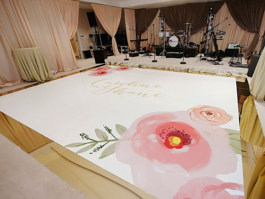 Wedding reception personalized dance floor pink flowers and gold names in calligraphy center