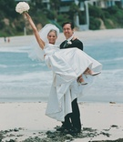 Groom holds bride on Laguna Beach sand