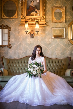 asian bride in berta ball gown with sparkling skirt and large bouquet