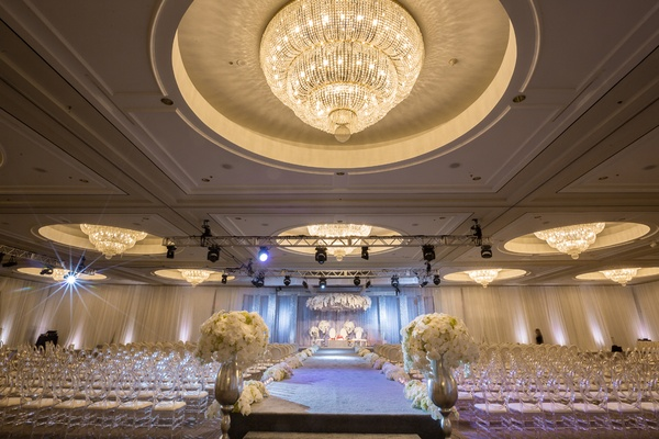 opulent white ceremony space ballroom florals aisle ghost chairs california indian hindu wedding