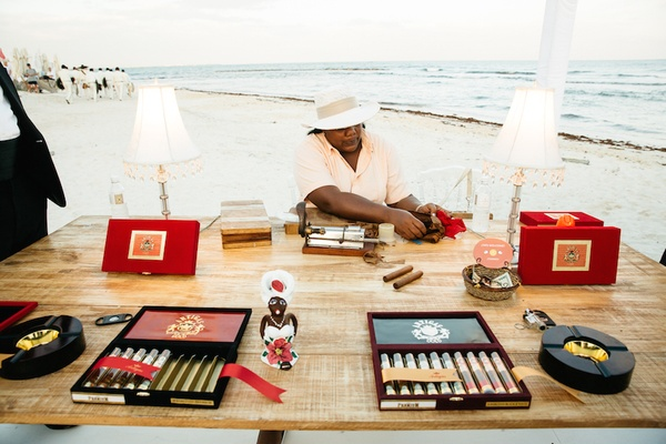 A gentleman rolls cigars at a beach wedding in Playa del Carmen, Mexico