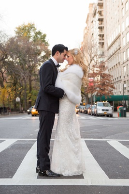 a bride and groom embrace one another in the crosswalk of a street in new york city