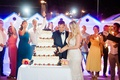 bride & groom cutting traditional italian wedding cake while guests hold sparklers in the background