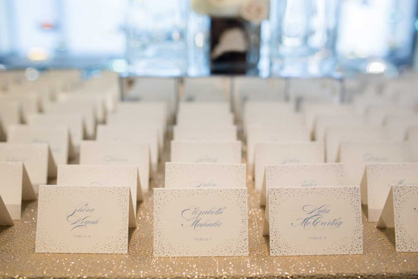 wedding escort cards on sparkly linen light blue confetti motif light blue calligraphy