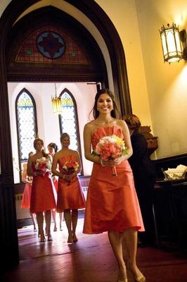 Bridesmaids in short dresses walk down church aisle