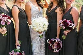 Bride in Naeem Khan wedding dress holding white bouquet and bridesmaids in black dresses with purple