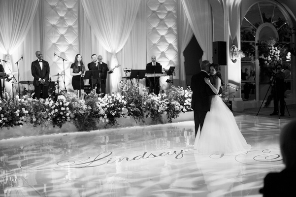 Black and white photo of bride dancing with father of bride on large dance floor with couple names