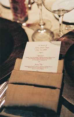 White menu stationery in gold linen napkin