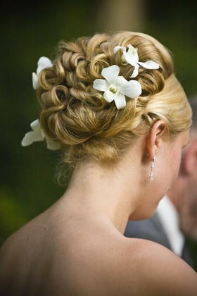 Curled wedding hairstyle updo with orchid flowers