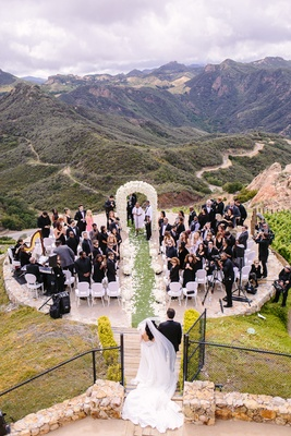 malibu rocky oaks ceremony, white chairs, ivory floral arch, bride in riki dalal couture