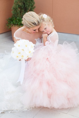 Bride with orchid bouquet and flower girl in pink ball gown tulle ruffle layer skirt