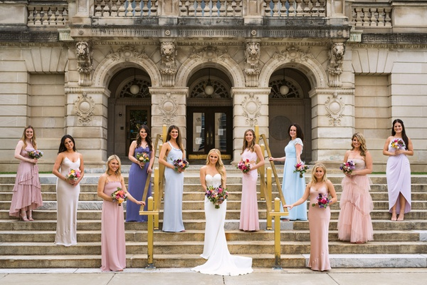 bridesmaids in pink, champaign, blue, and periwinkle standing on steps