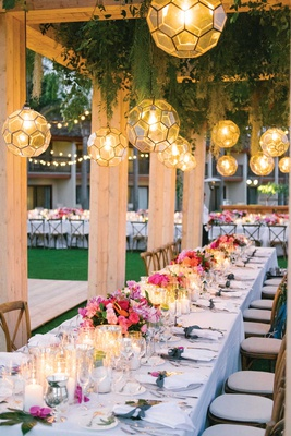Wood structure with lantern pendants greenery string lights pink flowers candlelight long table
