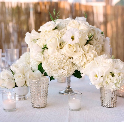 Beachside tented wedding reception with white linens, hydrangeas, roses, lisianthus in silver vessel