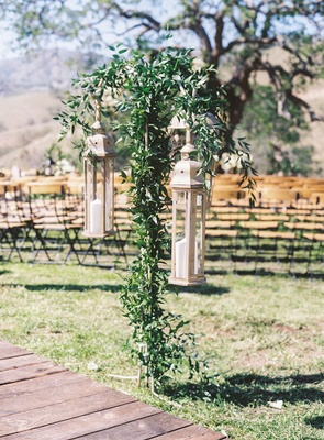 Antique lanterns with pillar candles along wood plank aisle