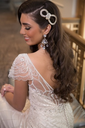 Bride with 1920s inspired wedding dress, chandelier earrings, and figure 8 headpiece