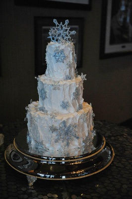 Frozen theme winter wedding cake with blue snowflakes and white frosting