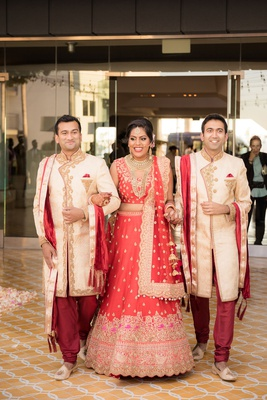 bride in red and gold lehnga gold jewelry brothers of bride walking her down aisle