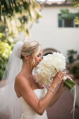 bride in strapless wedding dress and veil sniffing full bouquet of ivory roses