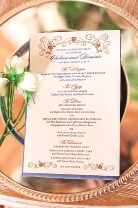 formal wedding menu with gold and blue details on reflective charger plate
