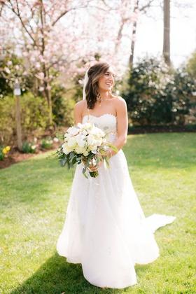 bride in reem acra wedding dress ivory flower bouquet greenery accents medium length hairstyle ideas