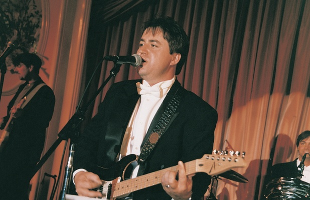 Formal groom on stage with electric guitar in tuxedo