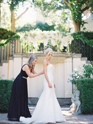 maid of honor in black a-line gown zipping up brides white trumpet gown outdoor ceremony space