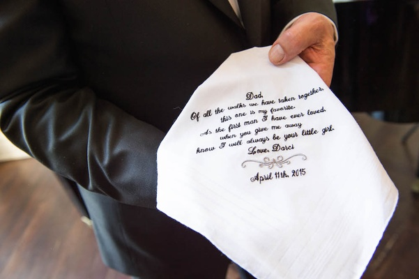 Father of bride holding sentimental handkerchief with embroidered letter