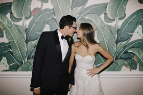 bride in strapless wedding dress long hair groom in tuxedo bow tie glasses beverly hills hotel palm