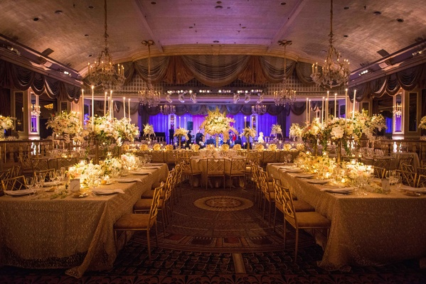 reception with white tablescapes with long tables tall floral arrangements candles purple uplighting