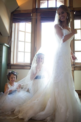 flower girls play under brides veil bride smiling flower crowns sash dresses