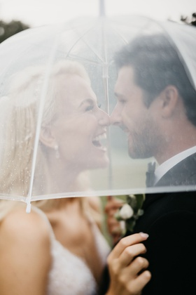 bride former miss america savvy shields under clear umbrella rainy day wedding with groom happy