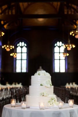white wedding cake with fresh white ranunculus flowers on top candles on table