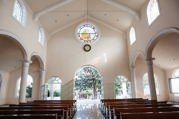 White interior, stained-glass window, wood benches at Nuestra Señora de Guadalupe, Playa del Carmen
