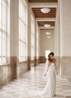 Bride in lace wedding dress long sleeve illusion sheer details and veil hair swept to one side