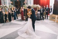 bride in romona keveza, groom in tuxedo kissing on middle of dance floor