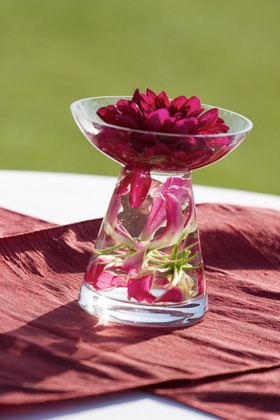 Glass vase with lilies under water and dahlia in bowl on top