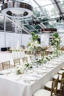 Wedding reception in glass tent with circular chandeliers and hanging glass spheres