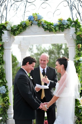 Bride and groom exchanging vows outside