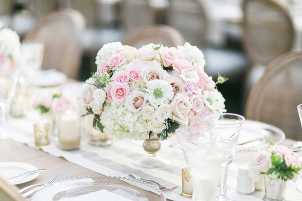 Wedding reception centerpiece with white hydrangea, white rose, and pink rose flowers